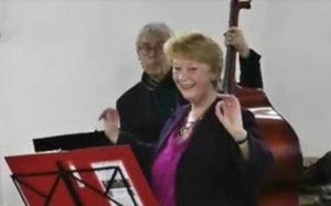 Inloopkoor Kantado Festivalo Grote Kerk Beverwijk met dirigente Hetty Kienhuis – Screenbeeld van film Henk Jansen